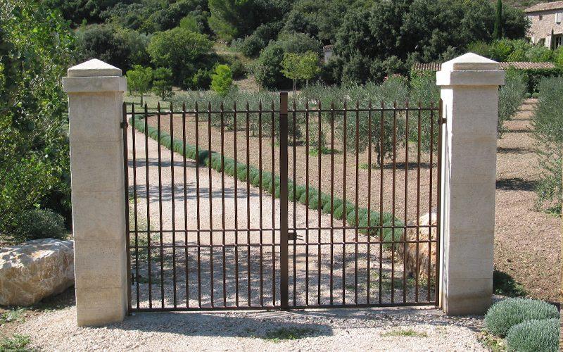 Portail 2 vantaux avec barreaudage rond et pointes de défense et pilastre